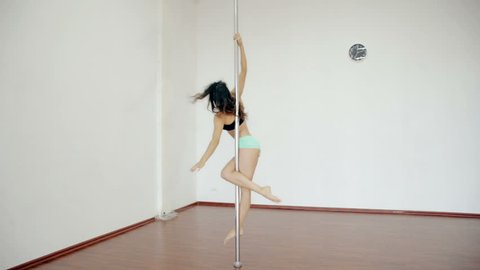 Wide shot Young girl dancing poledance in white room