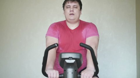 Man overweight tired on exercise bicycle