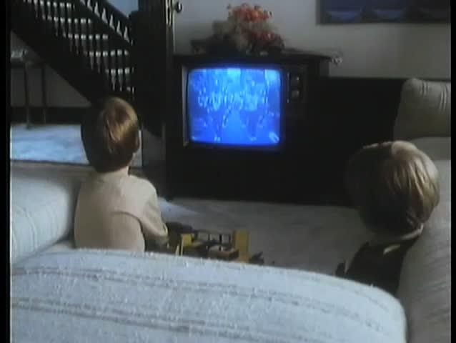 Children watching parade on television