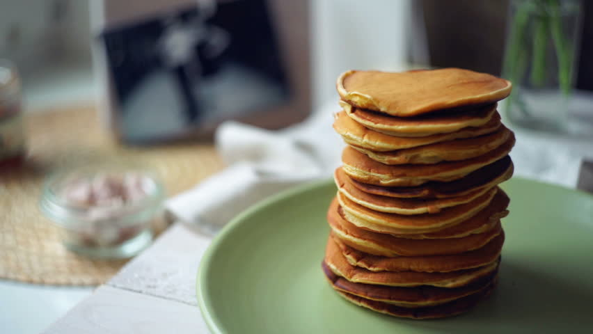 Man hand puts piece of butter on stack of pancakes pancake jam pouring on pancake stack strawberry jam on stack of golden pancake pancakes with ccuart Image collections