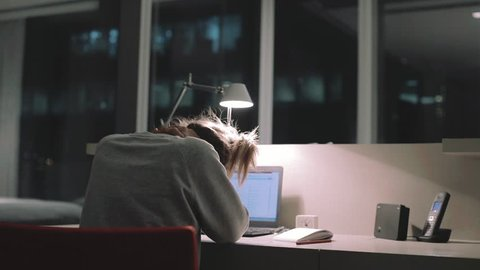 Young concentrated woman, sitting in her room or office with french windows in the dark at the lamp.Studies late at night.Staying up late. Woman feeling headache and pain in the neck.