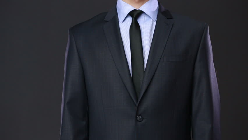 Young man in white shirt and suit tying a tie on a white business man hiding money in pocket on black background hd stock video clip ccuart Choice Image