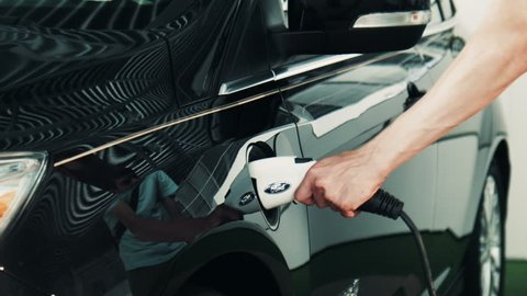 Man inserting power plug to charging port on front side of black electric car in showroom