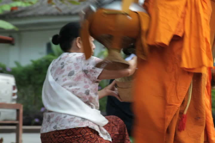 LUANG PRABANG, LAOS - OCTOBER 27: Two women give sticky rice to monks during the