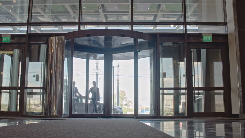 Businesswoman and her two male colleagues entering office building through revolving door and looking around. Man showing direction and they walking together