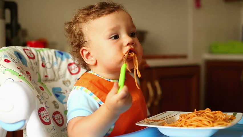 Baby is eating spaghetti with a fork