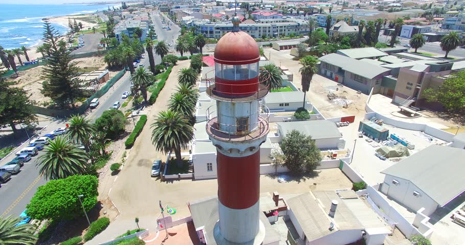 Aerial view drone video of Namibian Atlantic coastline, Swakopmund Lighthouse and beach, surf break line and landscape with ocean background of Swakopmund town at Namibia's west coast