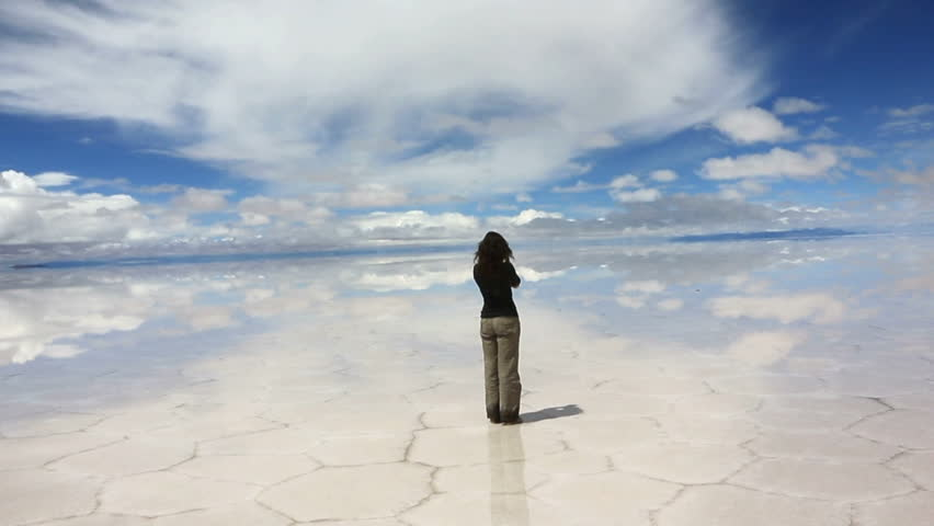 Woman taking pictures in the middle of the lake Salar de Uyuni, Bolivia