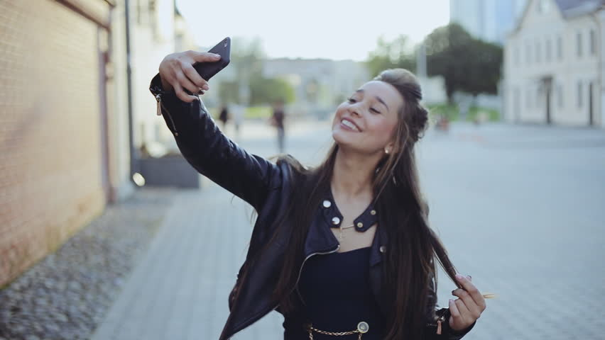 Young beautiful hipster woman using smart phone selfie in the city