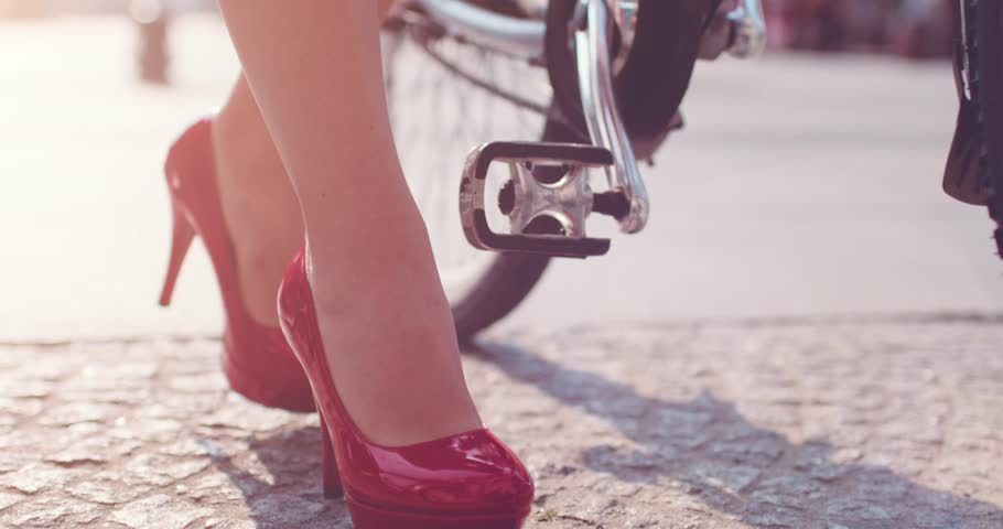 Business woman taking a bicycle form a city-bike station. Close up on feet. Slow Motion, 4K. Sexy female legs in red high-heeled shoes approaching bicycle and walking away with it.  Lens Flare.