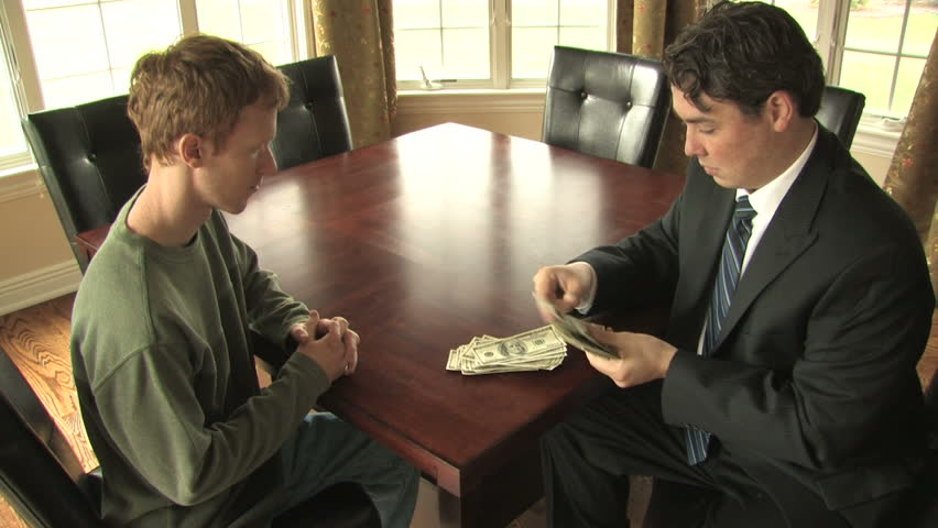 A businessman in a suit counts a stack of money and passes it to another man at a conference table
