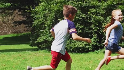 summer holidays, childhood, leisure and people concept - happy pre-teen kids playing tag game and running in park in slow motion mode