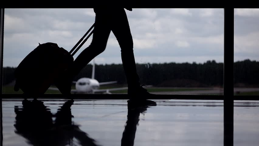 Female passenger legs silhouetted, girl walk with trolley case at airport terminal against glass wall window. Parked airliner seen outside, cloudy sky. Departure gate slow motion shot | Shutterstock HD Video #18675731