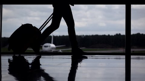 Female passenger legs silhouetted, girl walk with trolley case at airport terminal against glass wall window. Parked airliner seen outside, cloudy sky. Departure gate slow motion shot