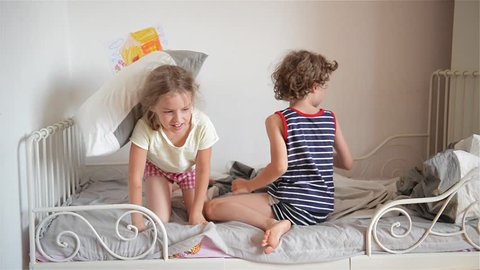 Boy throws a pillow at the girl who sleeps, Happy laughing brother and sister having a pillow fight