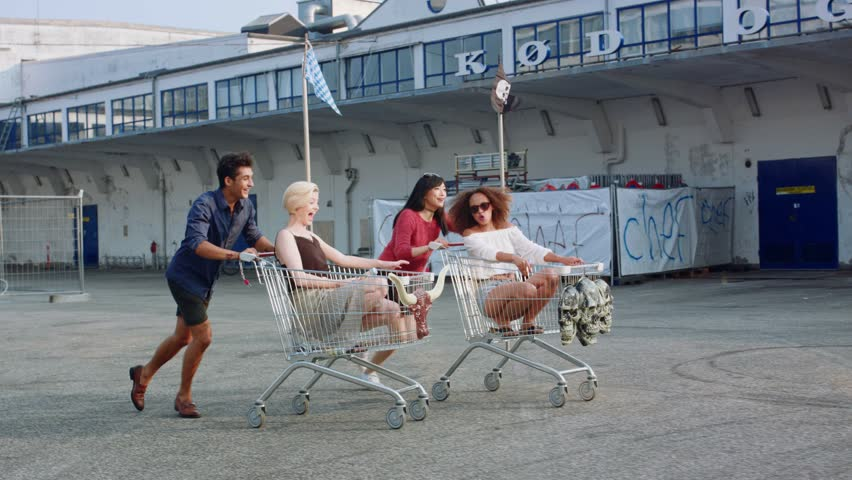 Young friends racing grocery carts. Multiracial group of young people enjoying outdoors with shopping trolley race.  | Shutterstock HD Video #18685001