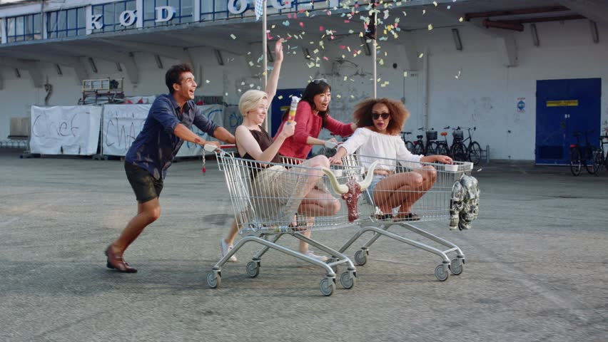 Young friends racing grocery carts. Multiracial group of young people enjoying outdoors with shopping trolley race.