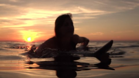 SLOW MOTION, CLOSE UP, DOF: Young happy woman paddling out on surf in deep ocean water at beautiful golden sunset. Girl relaxing on surfboard and enjoying her vacation on dreamy Zanzibar, Tanzania