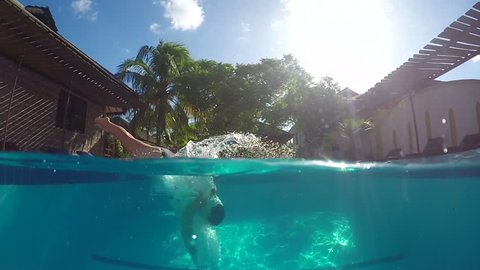 HALF UNDERWATER, SLOW MOTION, CLOSE UP: Happy young woman jumping headfirst into swimming pool on the garden at fancy tourist accommodation apartment. Cheerful girl on fun summer vacation diving
