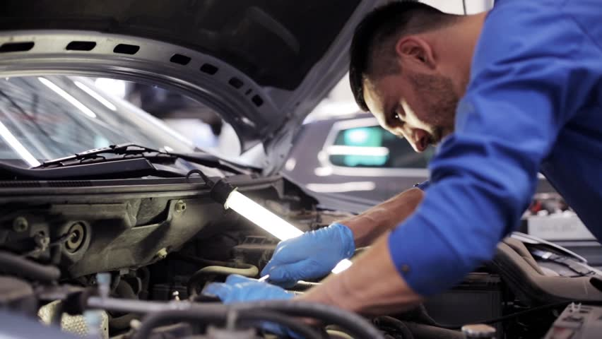 car service, repair, maintenance and people concept - mechanic man with wrench and lamp working at workshop