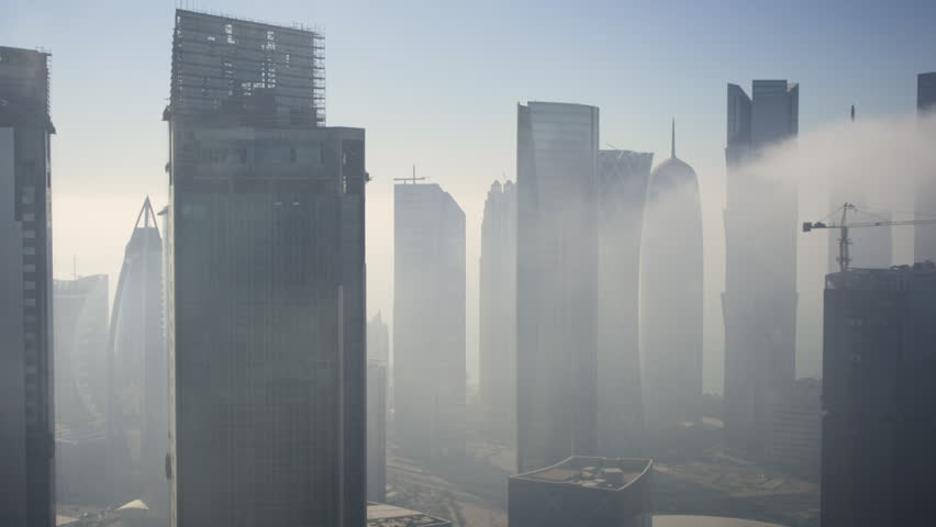 Panning across the new skyline of the West Bay central financial district of Doha, in early morning fog, Doha. Qatar, Middle East