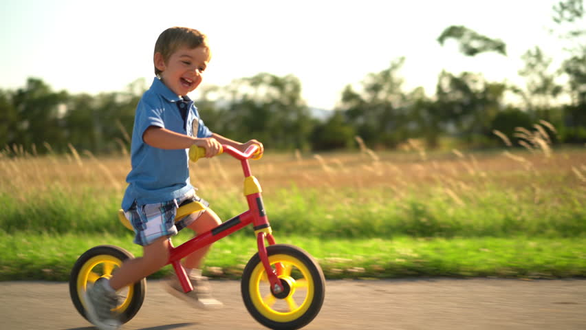 4k footage , laughing little boy having fun riding his bicycle on sunny afternoon