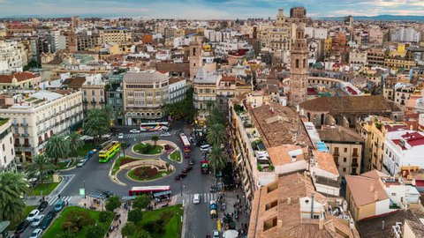 Aerial view of Valencia, Spain at sunset. Illuminated Plaza de la Reina with many cafes and restaurants and very popular among tourists. Cloudy colorful sky. Time-lapse