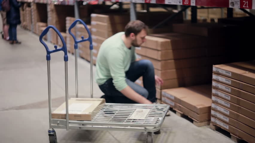 A man is taking a box from the shelf, putting it on the trolley, checking his list in a storage warehouse | Shutterstock HD Video #18772571