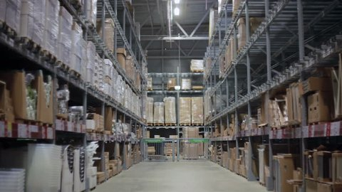 Camera moves between palettes with cardboard boxes and different materials in a storage warehouse