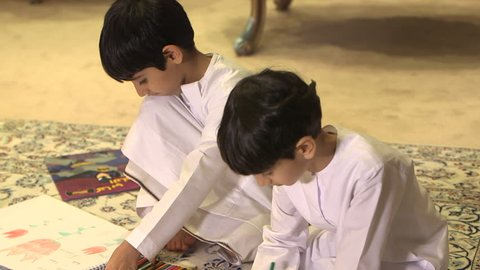 Abu Dhabi, UAE - CU tilt-up onto two Emirati boys playing with colouring pencils while sitting on a carpet. (Abu Dhabi, UAE-2013)