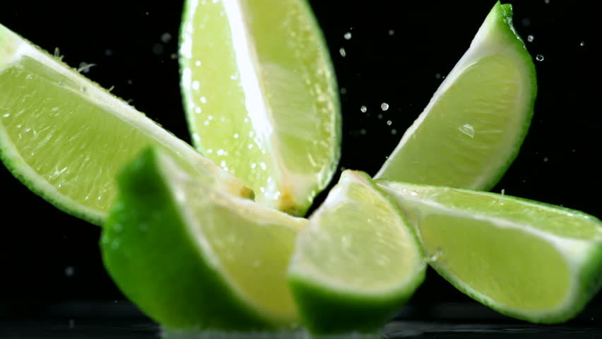 Slo-motion lime  falling into wedges against black drop #1881013