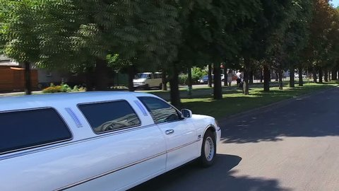 white limousine rides on the road in the summer