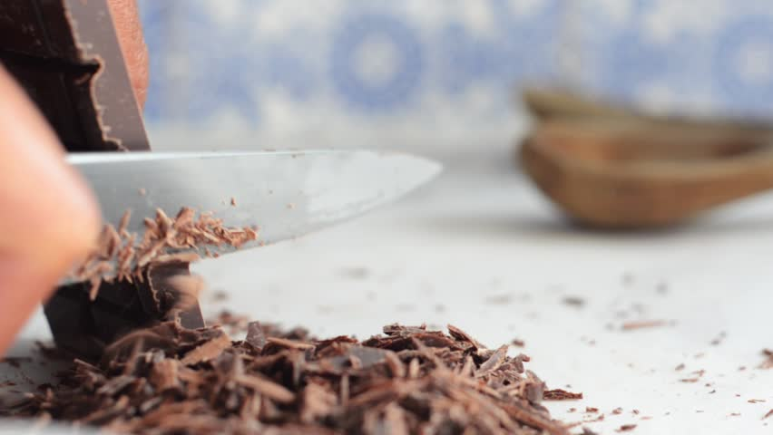Close up video of fine chocolate shavings being made by hand, sliced off the block with a knife, eye level, on white marble counter top, with soft focus blue and white tiles in background.