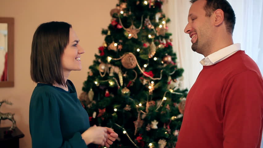 Man giving gift to woman in front of Christmas tree