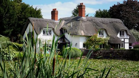 old English thatched house in front of mill pool - Badger, Shropshire, England: August 14th 2016