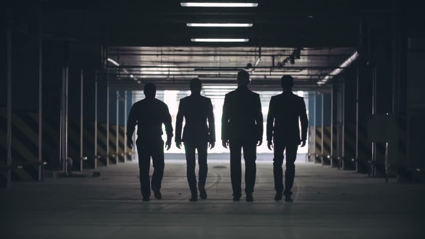 Slow motion locked-down rear view of silhouettes of four men in black suits confidently walking away from camera towards exit of parking lot.