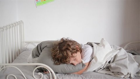 Overslept boy does not want to wake up, child falls out of bed