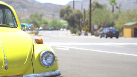 Yellow VW Bug oldtimer in great condition parked on the side of the road, some traffic in background