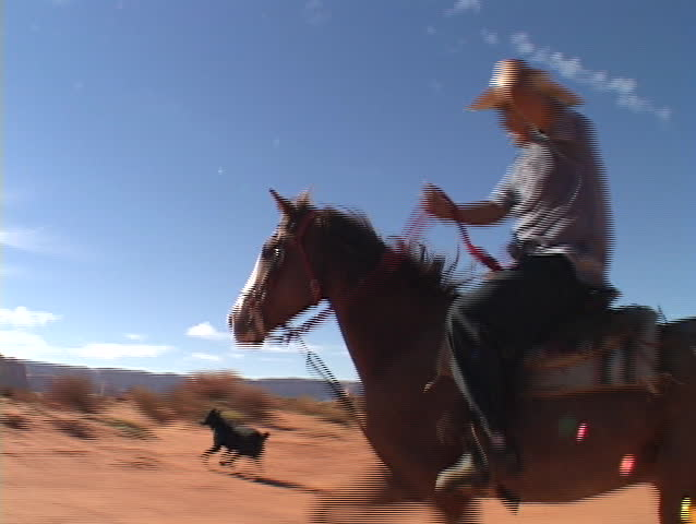 A cowboy on horseback rides fast across the Utah desert.