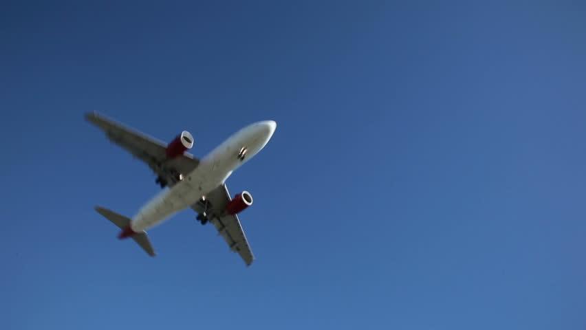 Jet plane approaching landing across blue sky