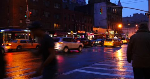 NEW YORK CITY - CIRCA MAY 2015: Street view of people walking and traffic in Manhattan at dusk while raining.