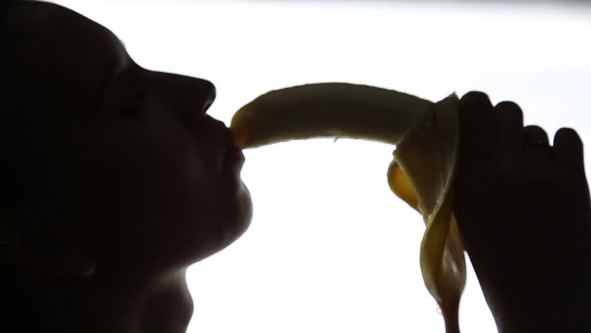 Close-up of Young amazed woman holding a banana, she is going to eat a banana. she sucks a banana