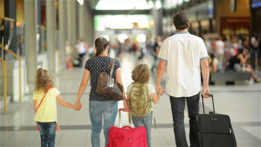 Happy family with little girl and boy going on railway station, mother father and the kids walk through the airport with suitcases | Shutterstock HD Video #18966433