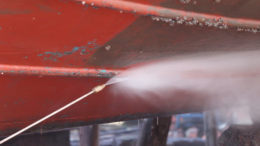 A man working on pressure washer to cleaning boat hull barnacles antifouling and seaweed at the harbor