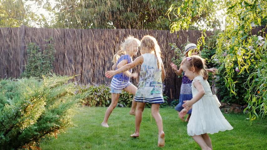 Children playing in the summer garden. Grupa children have fun under water jets or rain