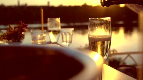 Pouring Champagne. People toasting and drinking champagne on the restaurant terrace over sunset. Celebrating. Glasses with Sparkling Champagne over nature Background. Resort. Slow motion full hd 1080p