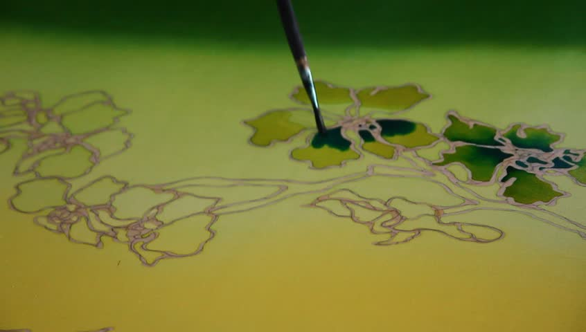 Close-up of an artist carefully paint the floral/flower motif on a yellow traditional batik fabric
