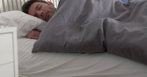 Sleeping man wakes up in a double bed, sits up and drinks from a glass of water on bedside table.  Camera move on jib arm.  Side view, medium shot.