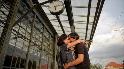 Happy couple embracing on railway station platform. Farewell at the train station, young girl and guy talking on platform