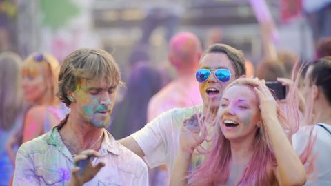 Happy guys jumping and dancing to music at concert, joking and laughing together. Drunk young people in color powder relaxing at outdoor party together, youth spirit, fun in Holi festival atmosphere